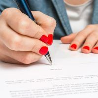 Business woman with ballpoint pen signing contract document